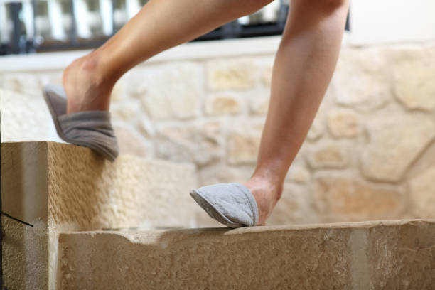 Woman legs stumbling going down the stairs stock photo