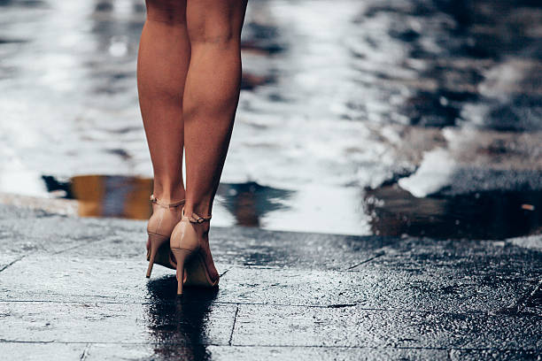 Woman legs under the rain in front of the road stock photo