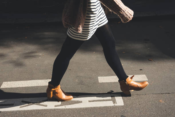 Woman legs walk on street in brown shoes. stock photo