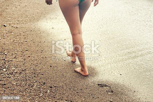 istock Woman legs - Walking on the beach, on the seashore 992837188