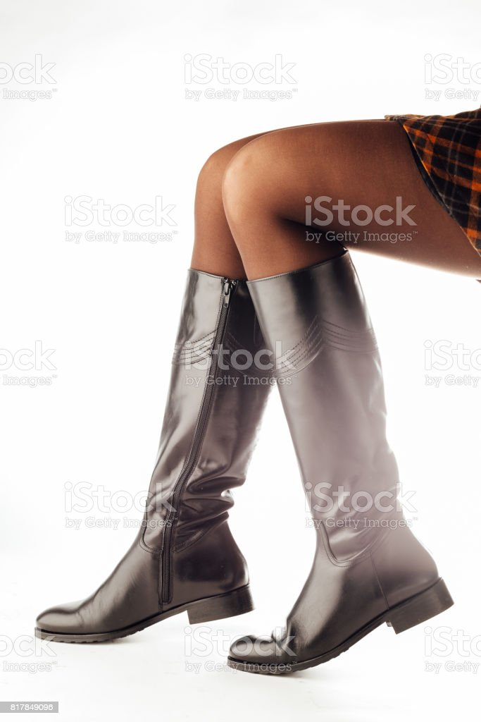 woman legs wearing black leather high boots stock photo