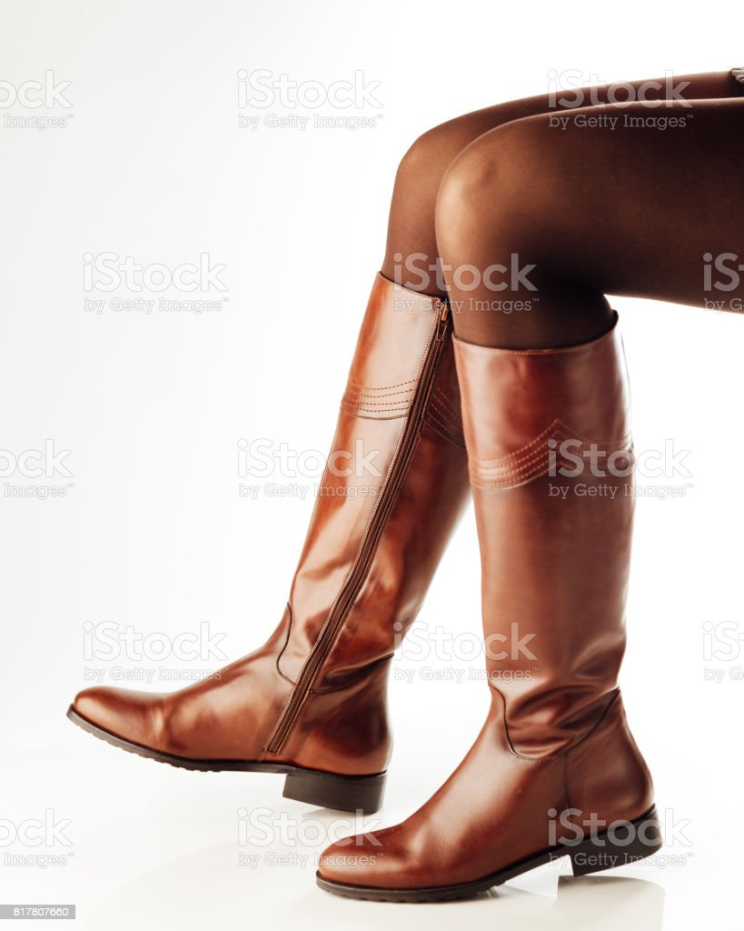 woman legs wearing brown leather high boots stock photo