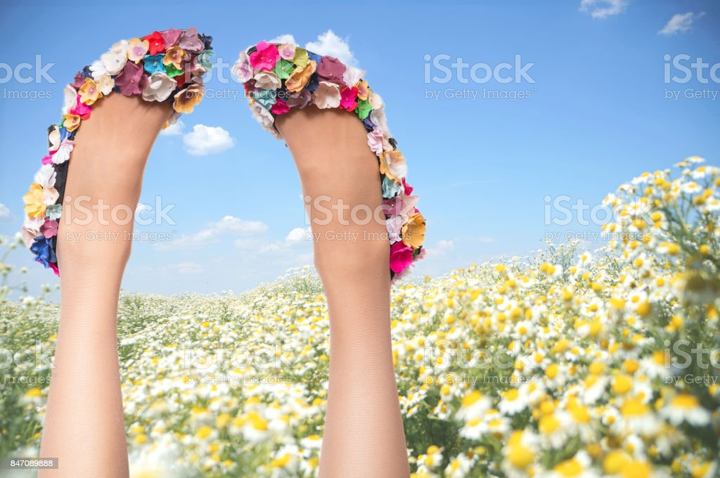 Woman legs wearing summer shoes over field and sky background - Royalty-free Adult Stock Photo