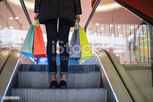 istock Woman legs with colorful shopping bags on the escalator in a shopping mall 880499484