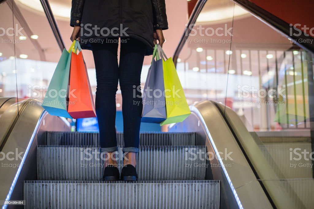Woman legs with colorful shopping bags on the escalator in a shopping mall stock photo