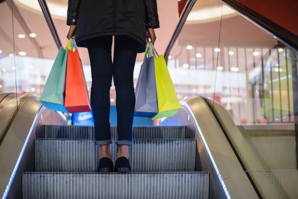 woman legs with colorful shopping bags on the escalator in a shopping mall - shopping mall stock photos and pictures