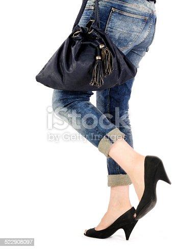 636803682 istock photo woman legs with fashion bag 522908097