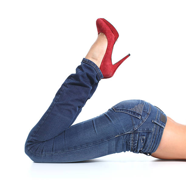 frau beine mit jeans und rote high heels - enganliegende jeans outfits stock-fotos und bilder