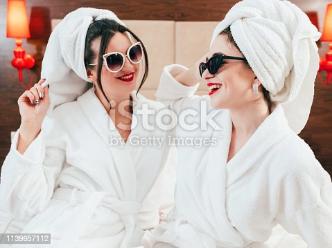 Woman leisure. Beauty care lifestyle. Two smiling females in sunglasses, bathrobes and turbans. Fun and joy time.