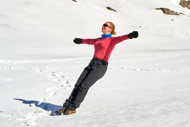 woman letting herself fall on her back in snow with her arms spread out - trust exercise. location: bucegi mountains, romania. - mulher deixar ir imagens e fotografias de stock