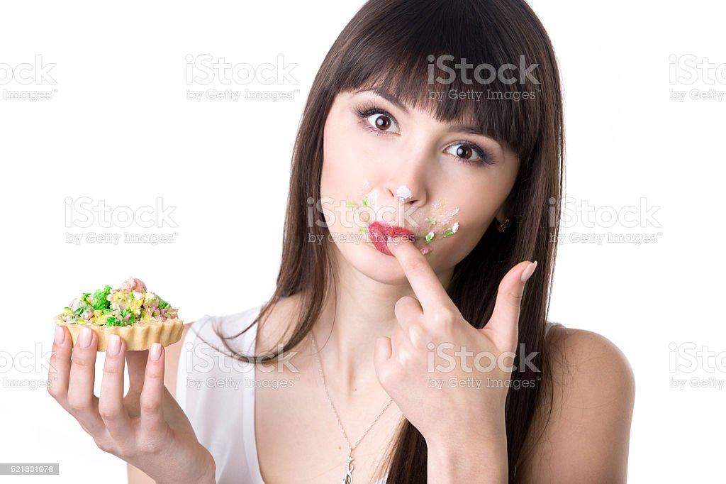 Mulher lambendo seus dedos enquanto comendo bolo - foto de acervo