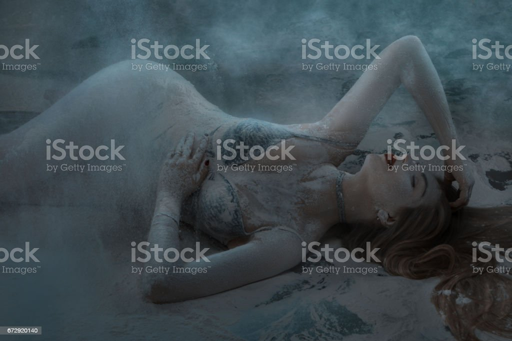 Woman lies on a floor in white flour. stock photo