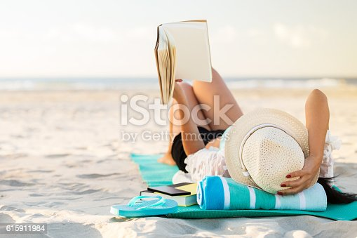 A woman lies on her back on the beach. She is holding up a hard cover book. She is lying on a mat with a rolled up beach towel underneath her head. She is also wearing a straw hat. A pair of flip flops, smart phone and another book are beside her. The sandy beach and ocean are blurred in the background. Copy space is available.
