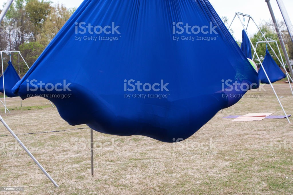 Woman Lies Suspended In Fabric Cacoon At Aerial Yoga Class - Royalty-free Adult Stock Photo