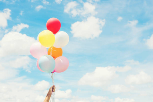 Woman Lifestyle concept : woman hand holding a bunch of colored balloons with blue sky. stock photo