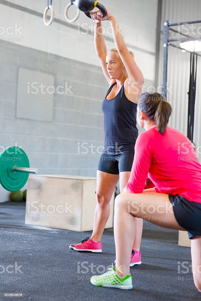 Woman lift kettlebells weights with personal trainer stock photo