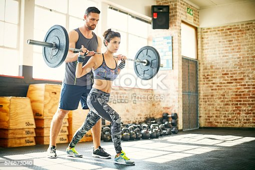 Full length of woman lifting barbell while fitness instructor assisting her doing clean and jerk. Determined female and male are in gym. They are in sports clothing.