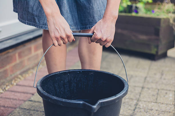 Woman lifting bucket in garden stock photo