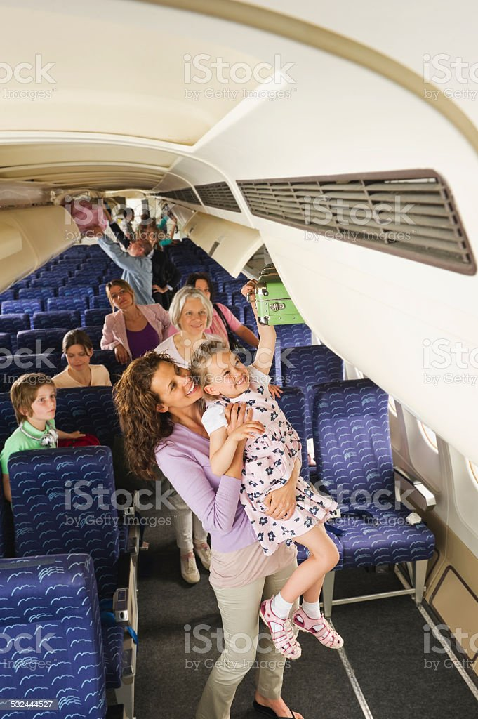 Woman lifting child reaching for hand luggage on airplane stock photo