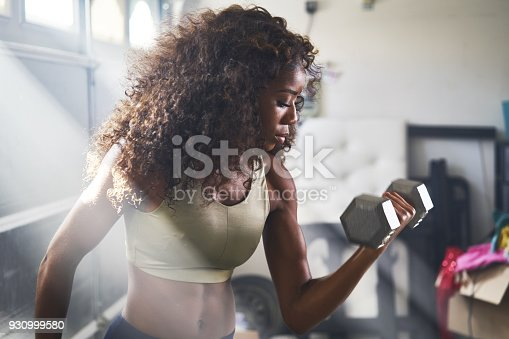 930998708 istock photo woman lifting dumbbell in home gym 930999580
