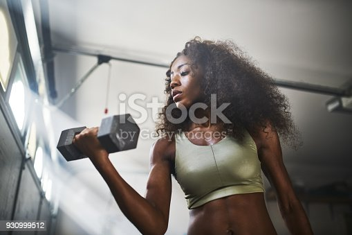 930998708 istock photo woman lifting dumbbell 930999512