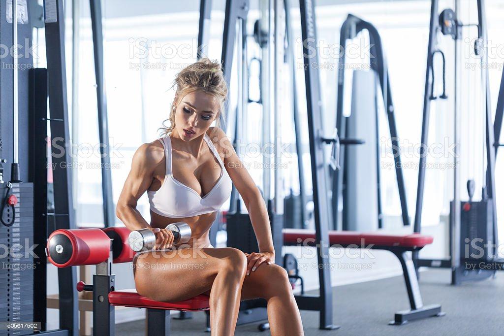 Frau heben Kurzhanteln im Fitnessraum – Foto