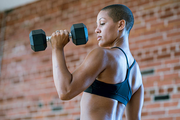 Woman Lifting Dumbbells An athletic and muscular woman is lifting dumbbell weights at the gym. bicep stock pictures, royalty-free photos & images