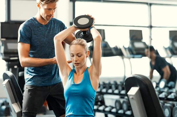 mujer levantamiento de pesas - entrenador personal fotografías e imágenes de stock