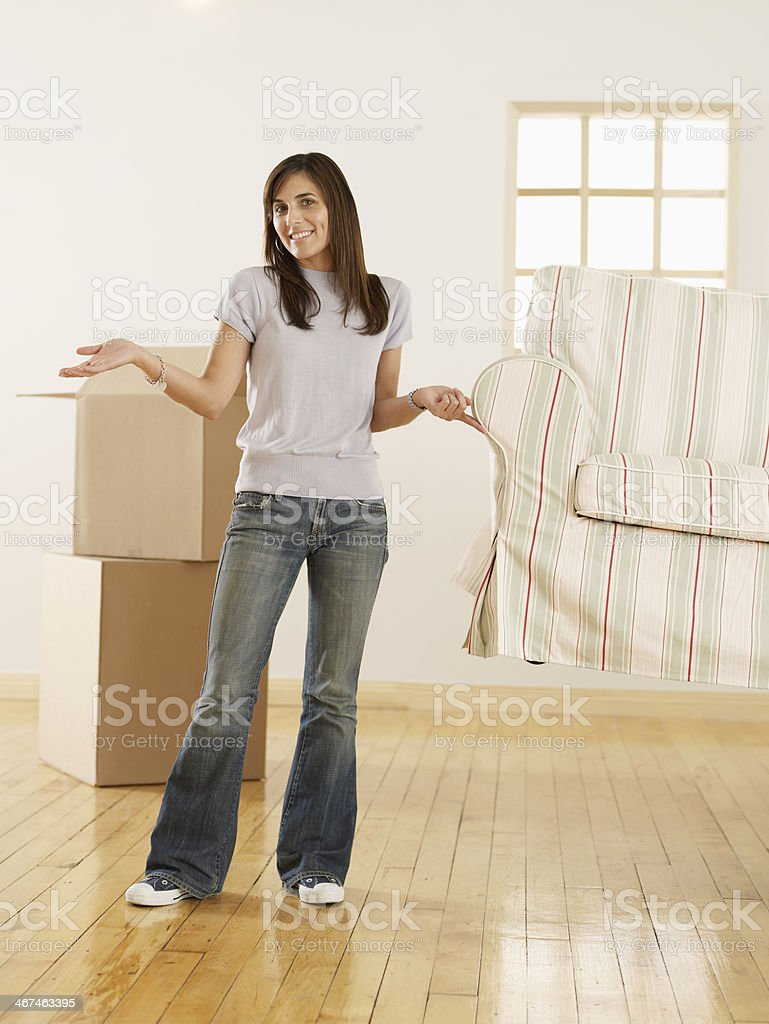 Woman Lifting Sofa with One Finger stock photo