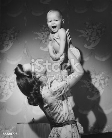 istock Woman lifting up baby (6-9 months) at home, (B&W) 57539225