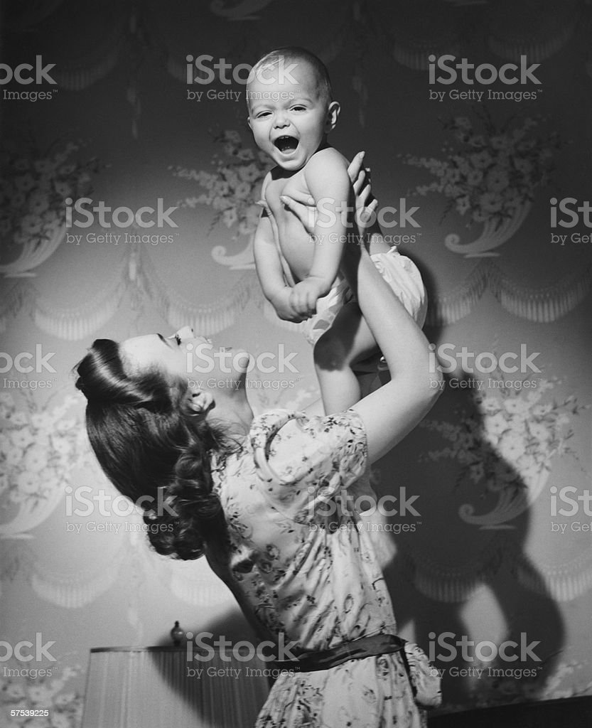 Woman lifting up baby (6-9 months) at home, (B&W) stock photo