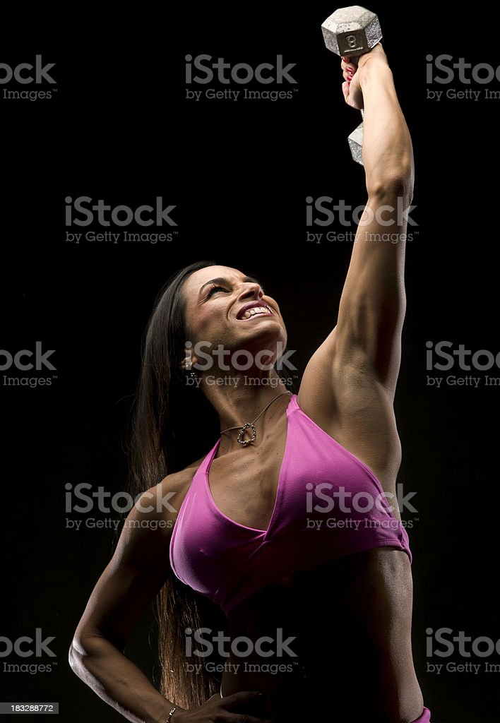 Woman lifting weight high in the air with one hand royalty-free stock photo