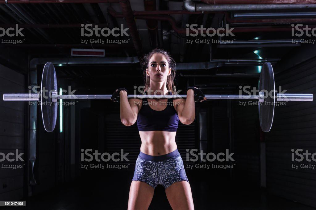 Woman Lifting Weights in Gym stock photo