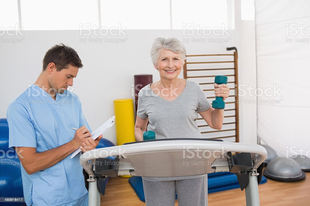 Woman lifting weights on treadmill while trainer writing notes stock photo