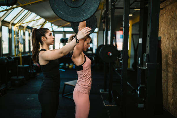 Woman lifting weights with a help of fitness instructor stock photo