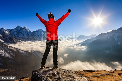 istock Woman lifts her arms in victory, Mount Everest National Park 507910624