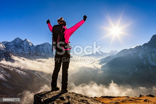 istock Woman lifts her arms in victory, Mount Everest National Park 589563772