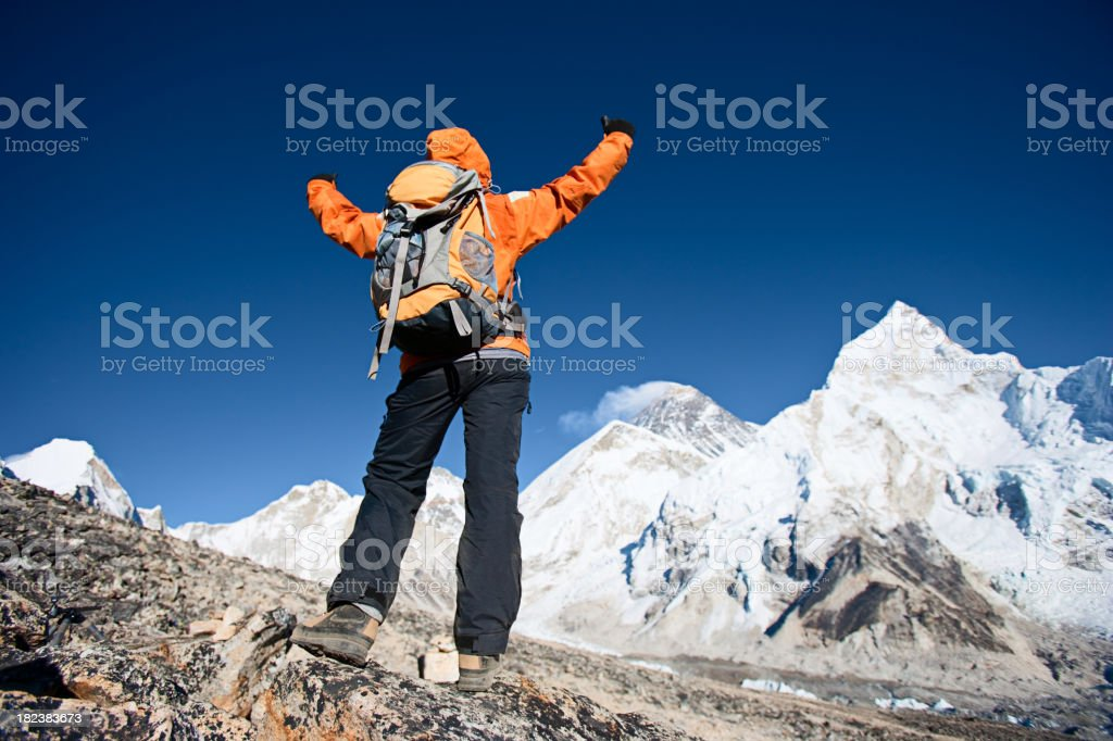 Woman lifts her arms in victory, Mount Everest on background royalty-free stock photo