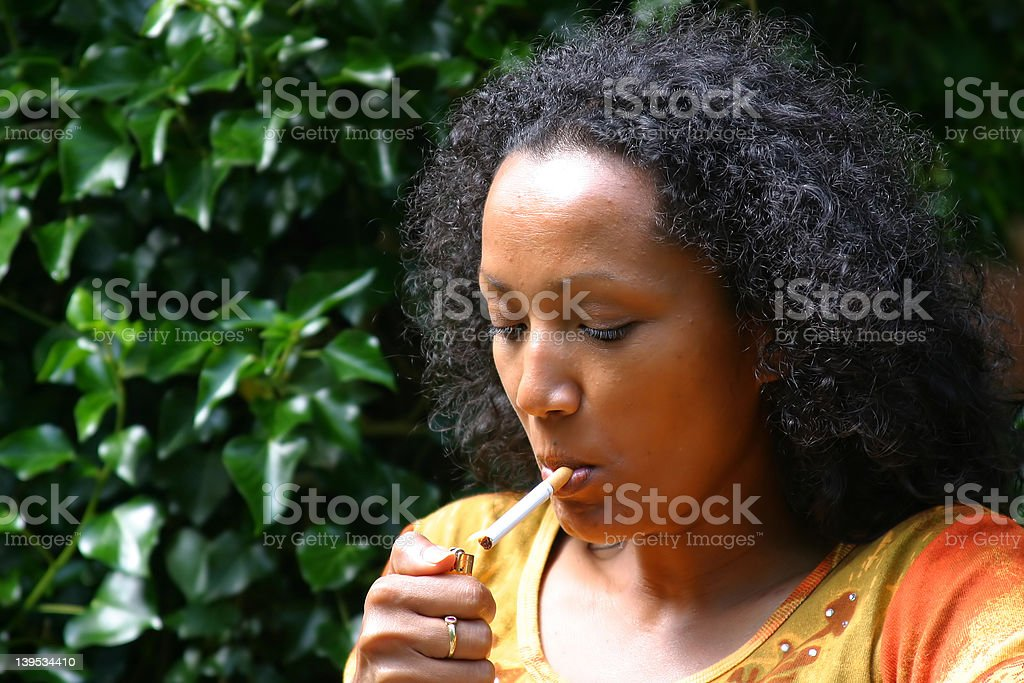 Woman lighting a cigarette stock photo