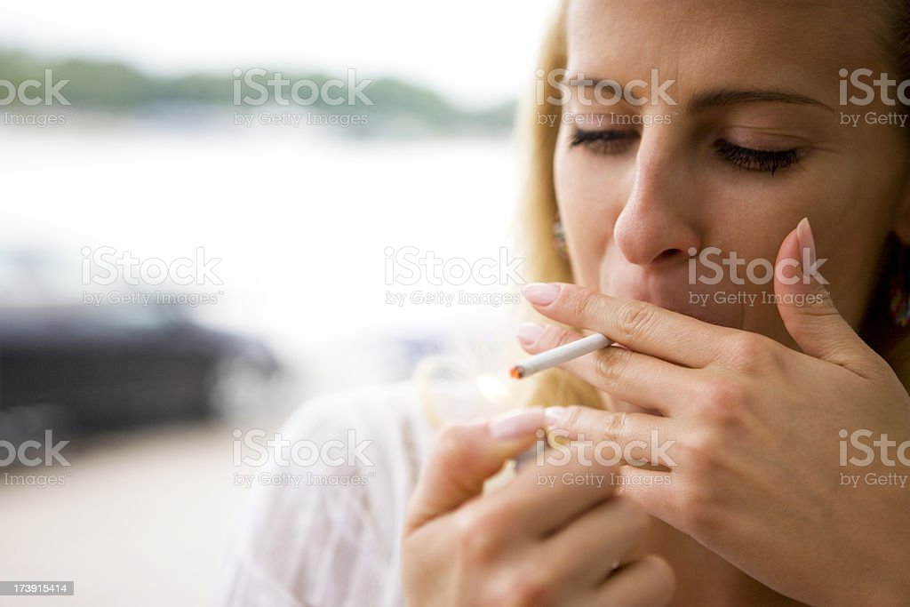 Woman lighting a cigarette royalty-free stock photo