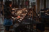 Woman lighting candle in church