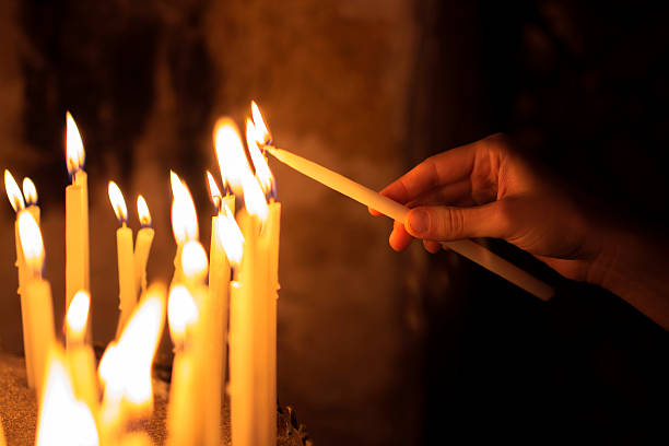 woman lighting candles  in a church stock photo