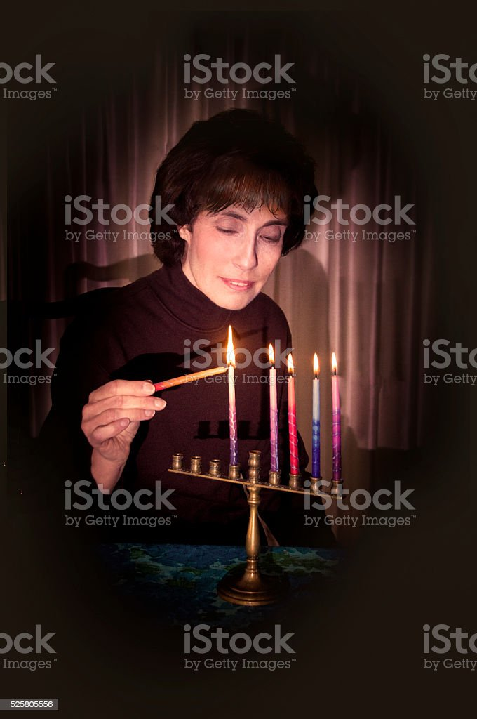 Woman lighting menorah stock photo