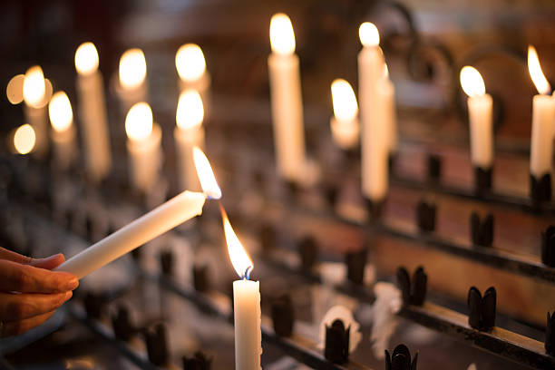 Woman lighting prayer candle Woman lighting prayer candle aka offering, sacrificial or memorial candles lit in a church catholicism stock pictures, royalty-free photos & images