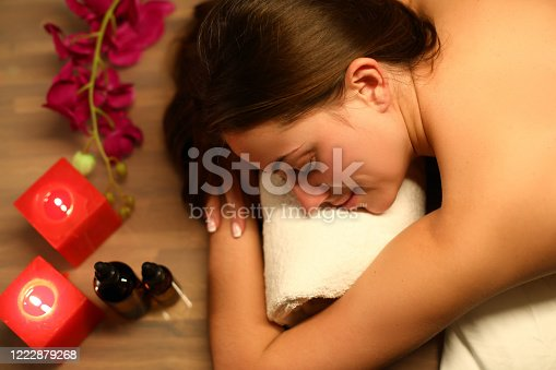 Woman likes spa treatments in salon, near candles. Woman feels tired and needs to be restored. To tune up body for regeneration and energy boost. Woman feels like queen, being at top bliss