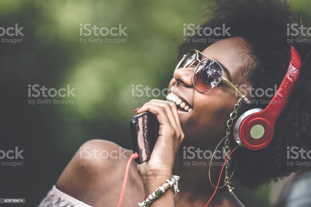 Woman Listening Music at Park stock photo