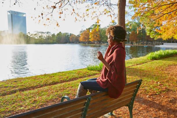 Woman listening music in the autumn park stock photo