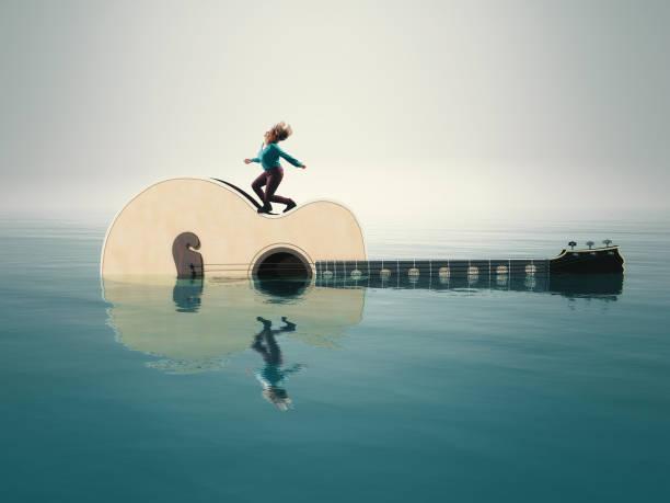 frau, die musik auf einer gitarre im wasser hört. - wärmeplatte stock-fotos und bilder