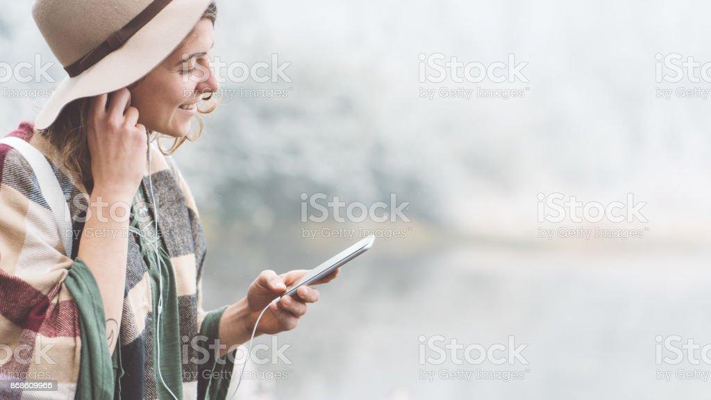 Frau Musik hören mit ihrem Handy im ersten Schnee – Foto
