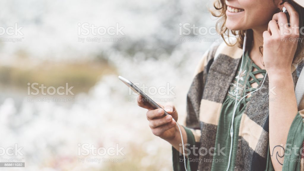 Woman listening music with her mobile phone in first snow stock photo